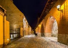 有古老堡垒墙壁的,夜照片狭窄的中世纪街道在老里加市,拉脱维亚 图库摄影