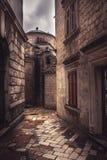 有古老石摊铺机的葡萄酒中世纪狭窄的绕街道有中世纪建筑学的在老欧洲城市科托尔在Monteneg 免版税库存照片
