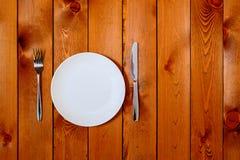 有古色古香的刀子的空的白色圆的在木背景的板材和叉子 与文本空间的顶视图 库存图片