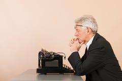 有古色古香的打字机的老人 免版税库存图片