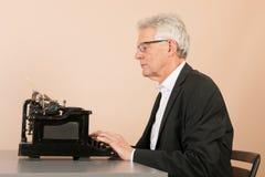 有古色古香的打字机的老人 免版税库存照片
