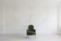 有古色古香的时髦的绿色扶手椅子的客厅在豪华白色墙壁设计浅浮雕灰泥造型roccoco元素 免版税库存图片