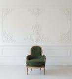 有古色古香的时髦的绿色扶手椅子的客厅在豪华白色墙壁设计浅浮雕灰泥造型roccoco元素 图库摄影