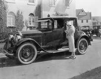 有古董车的妇女大房子外(所有人被描述不更长生存,并且庄园不存在 供应商保单 免版税库存照片