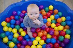 有可再用的尿布尿布的男婴在球池塘 库存照片
