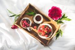 有可口早餐的盘子在床上 图库摄影