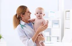 有可爱宝贝的儿童的医生在医院 免版税库存照片