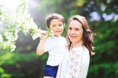 有可爱的儿子的美丽的母亲春天开花背景的  免版税图库摄影