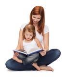 有可爱的小女孩和书的愉快的母亲 图库摄影