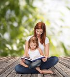 有可爱的小女孩和书的愉快的母亲 库存图片