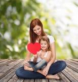 有可爱的小女孩和心脏的愉快的母亲 免版税图库摄影