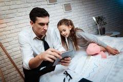 有可爱的尾巴的小女孩是对她的父亲` s工作感兴趣 与女儿的Buisnessman 免版税库存图片