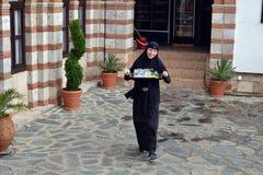 有可爱的微笑的一位美丽的年轻尼姑,一个传统风格的受欢迎的客人在圣Jovan Bigorski修道院里在Maced 图库摄影
