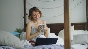 有可爱的快乐的妇女与使用膝上型计算机照相机的朋友的网上录影闲谈,当在家时坐床 免版税库存图片
