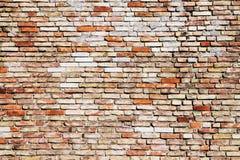 有可看见的裂缝的老和被风化的脏的黄色和红砖墙壁作为土气概略的纹理背景 免版税库存图片