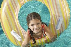 有可膨胀的圆环的女孩在游泳池 库存照片