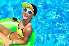 有可膨胀的圈子的愉快的魅力女孩在池边聚会夏天 免版税库存照片