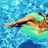 有可膨胀的圈子的魅力女孩在池边聚会夏天样式 库存图片