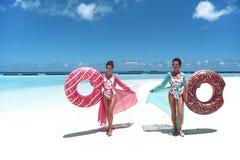?? 有可膨胀的多福饼浮游物床垫的愉快的自由的两名妇女 佩带薄绸海滩礼服享用的女孩异乎寻常 库存照片