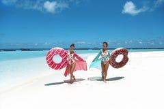 ?? 有可膨胀的多福饼浮游物床垫的愉快的自由的两名妇女 佩带薄绸海滩礼服享用的女孩异乎寻常 免版税库存照片