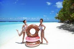 ?? 有可膨胀的多福饼浮游物床垫的愉快的自由的两名妇女 有时尚的游泳衣的女孩乐趣和享用 免版税库存图片