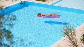 有可膨胀的床垫的可爱的女孩在室外游泳场 影视素材