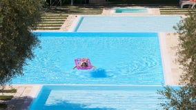 有可膨胀的床垫的可爱的女孩在室外游泳场 股票录像