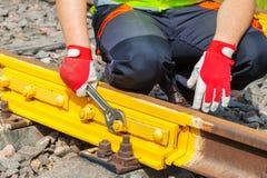 有可调扳手定象螺丝坚果的工作者在铁路轨道 免版税库存图片