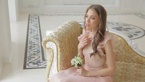 有可以百合美丽的花束的惊人的好淫女孩坐豪华沙发 股票录像