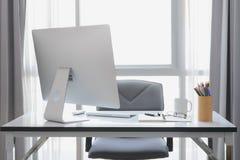 有台式计算机、咖啡和办公室equi的办公桌 库存照片