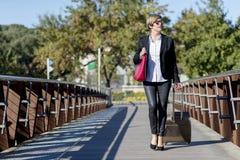 有台车袋子的女实业家走在城市环境里的 图库摄影