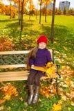 有叶子和文件夹的微笑的女孩 免版税库存图片