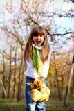 有叶子和玩具熊的呼喊的女孩 免版税图库摄影