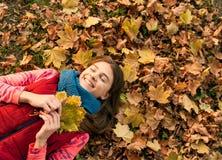 有叶子的女孩在秋天时间 库存照片