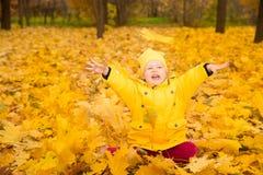 有叶子的愉快的可爱的儿童女孩在秋天公园 秋天 布加勒斯特c e办公室 免版税库存照片