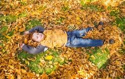 有叶子的愉快的可爱的儿童男孩在秋天公园 秋天 童年、家庭和孩子的概念 免版税库存图片