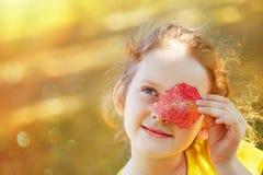 有叶子的漂亮的孩子在金黄秋天公园注视 免版税图库摄影