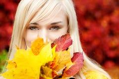 有叶子的美丽的年轻白肤金发的妇女 免版税库存图片