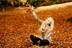 有叶子的美丽的年轻白肤金发的妇女 免版税库存照片