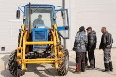 有司机和工作者的老蓝色白俄罗斯拖拉机 免版税库存照片