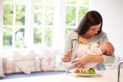 有吃健康膳食的婴孩的母亲在厨房里 免版税库存图片