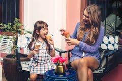 有吃在城市街道的孩子的妈妈冰淇凌 库存照片