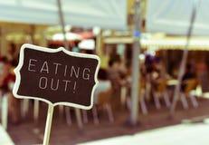 有吃在restaura的大阳台的文本的黑板 库存图片