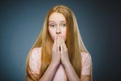 有吃惊的表示的小女孩,当站立反对灰色背景时 免版税库存照片