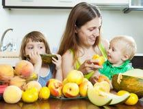 有吃果子的孩子的愉快的妇女 免版税库存照片