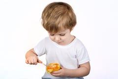 有吃的乳酪蛋糕松饼小男孩。 免版税库存照片