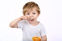 有吃的乳酪蛋糕松饼小男孩。 免版税库存图片