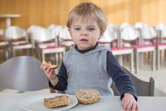有吃的面包和苹果小男孩在幼稚园 免版税图库摄影