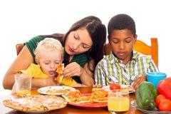 有吃薄饼的孩子的母亲 免版税库存照片