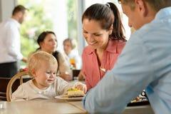 有吃蛋糕的子项的母亲和父亲 免版税库存图片